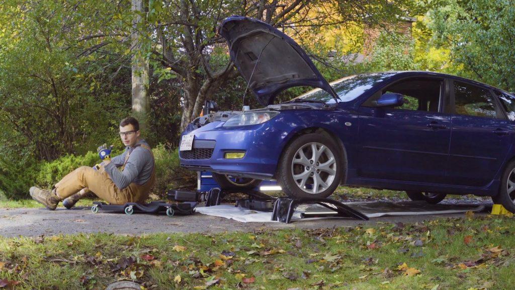 Une voiture est sur des rampes pour soulever le véhicule afin de procéder à un vindage d'huile.
