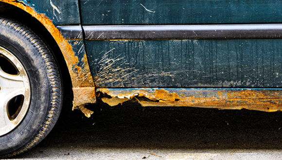 A dark green car with scale rust that has created holes on the fenders and undercarriage