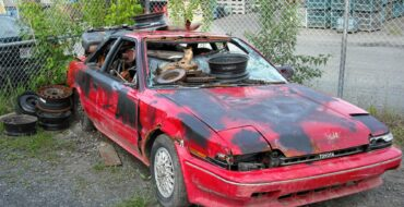 Red rusty Toyota is at the scrapyard