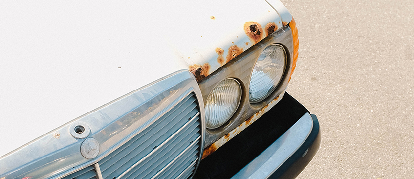Old white classic car with rust holes on the hood