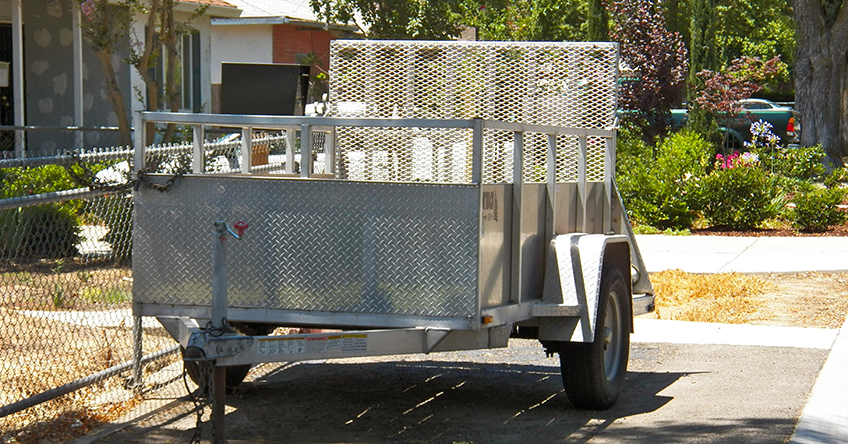 A utility trailer that is unhitched and parked in someone's driveway and needs trailer maintenance before it is towed