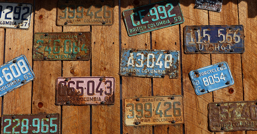 Several old and rusty Canadian license plates from British Columbia are pinned to a wooden wall