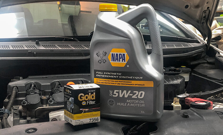 NAPA Premium Oil and NAPA Gold Oil Filter in front of an engine