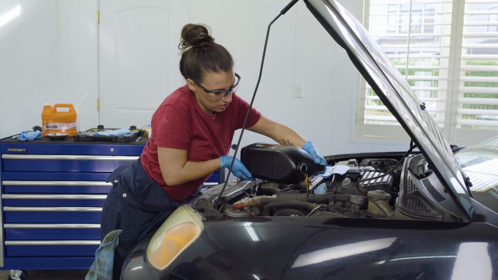 Person pouring pouring oil into their engine