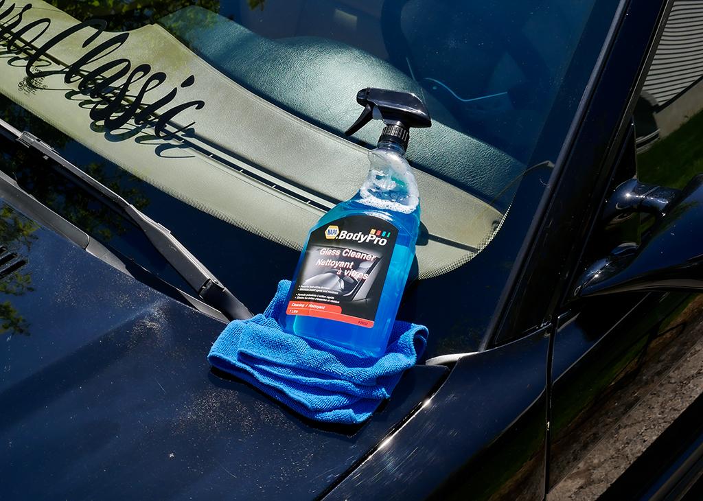 Le nettoyant pour vitres NAPA Body Pro (No de pièce: BPR 3032) posé sur le pare-brise propre d'une voiture.