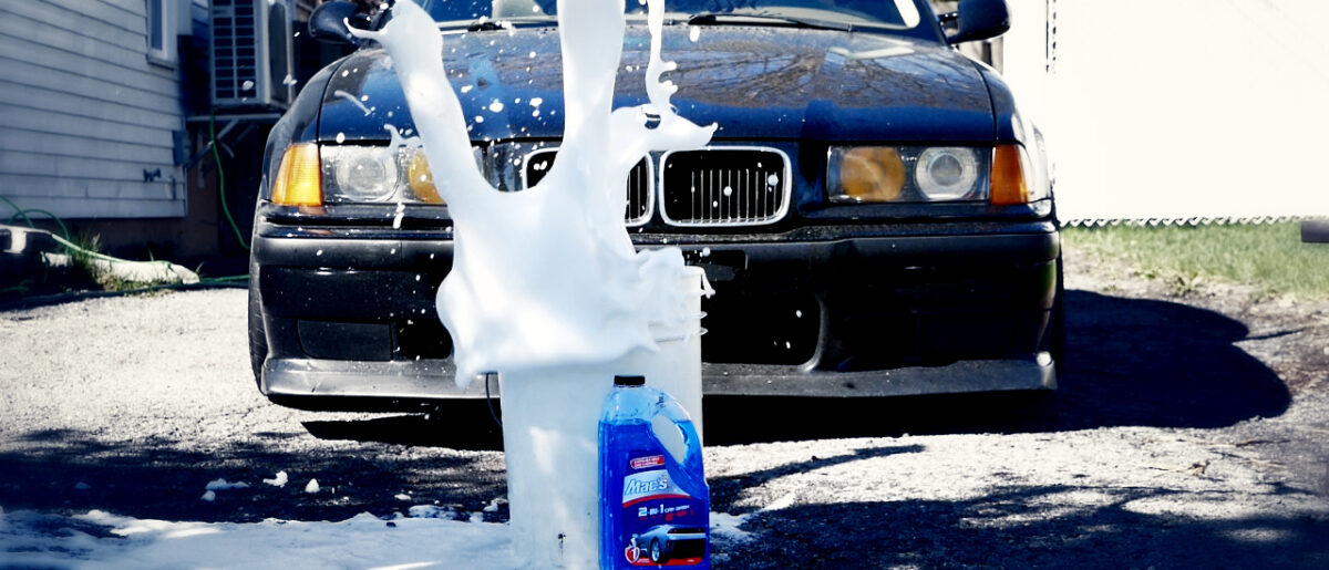 A car wash bucket in front of a black car with a big splash of soap flying from out of the bucket