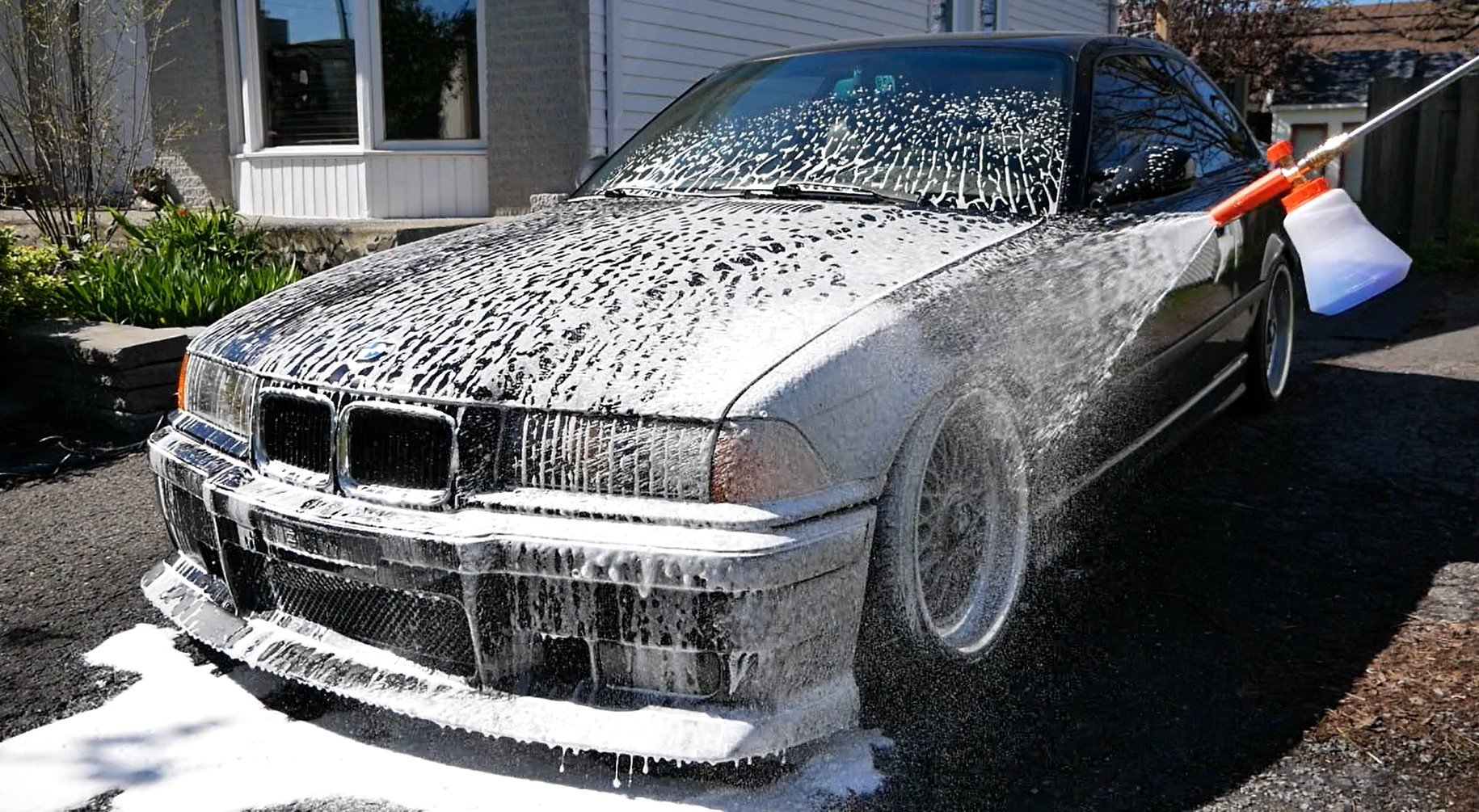 A black car being sprayed with snow foam using a foam cannon