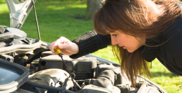 Woman checking the oil level of her car using a dip stick