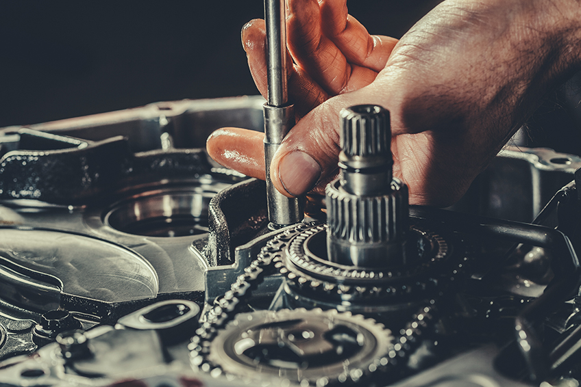 Oil covered hands working on transmission with socket wrench