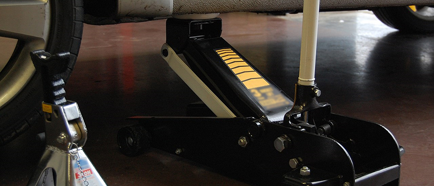 Floor jack lifting a vehicle and jack stands