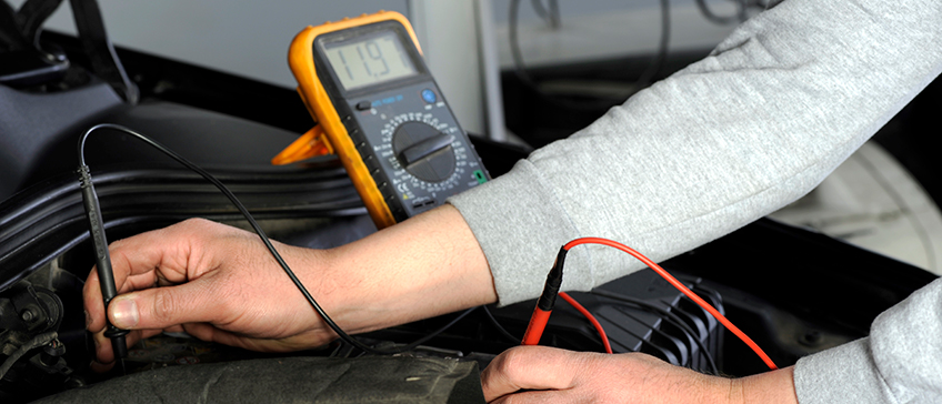 Person using a multimeter on their car to measure electrical components
