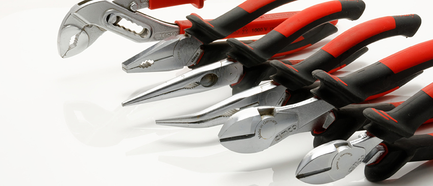 Different kinds of pliers in a row on a white background