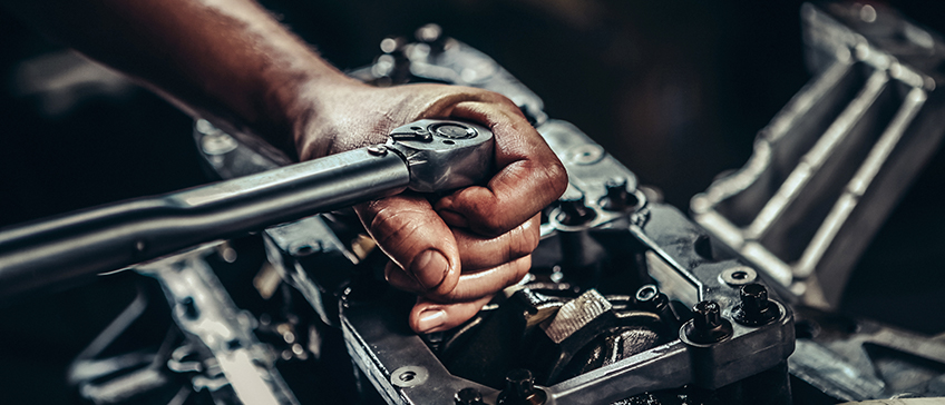 Person using a torque wrench to tighten engine bolts to torque specification