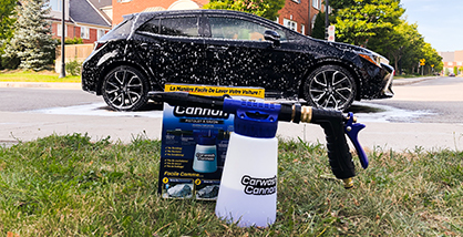 Car wash gun next to its product packaging on the grass with a black car covered in foam in the background