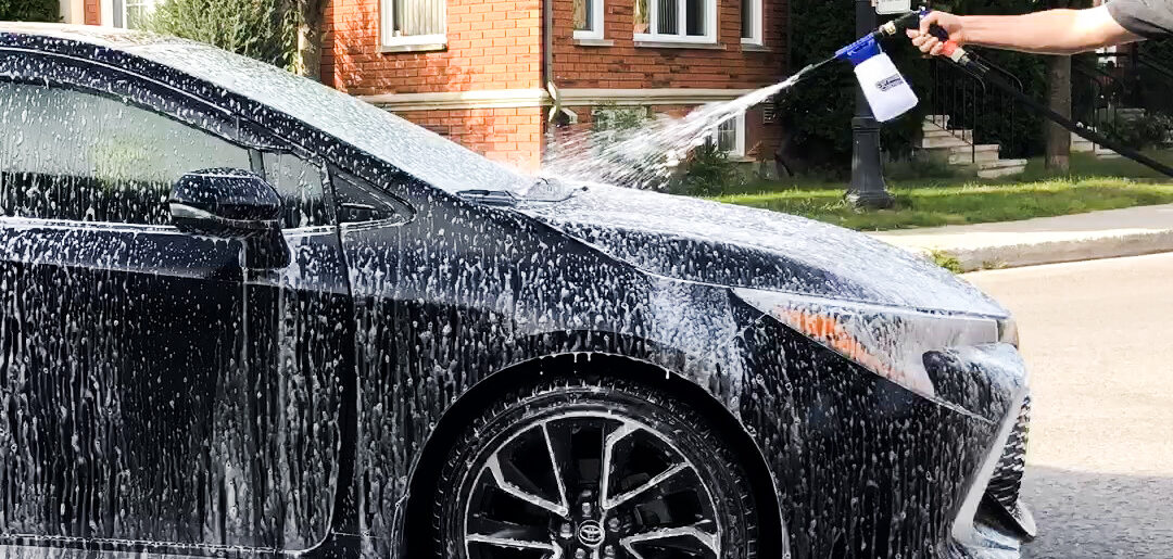 A black car being sprayed with a car wash gun and covering it in white foam