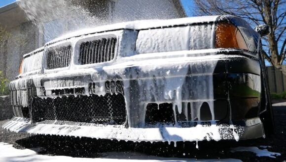 A black car with thick snow foam dripping off the front bumper