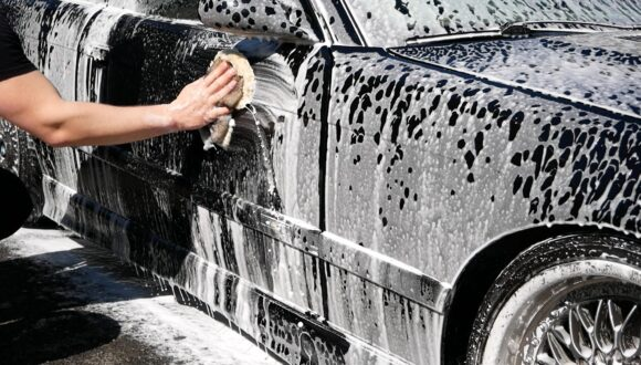 A black car covered in foam being scrubbed with a wash mitt
