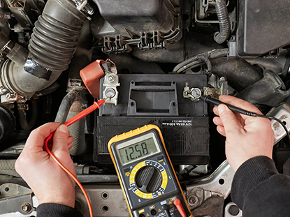 Person is checking their car battery voltage using a multimeter